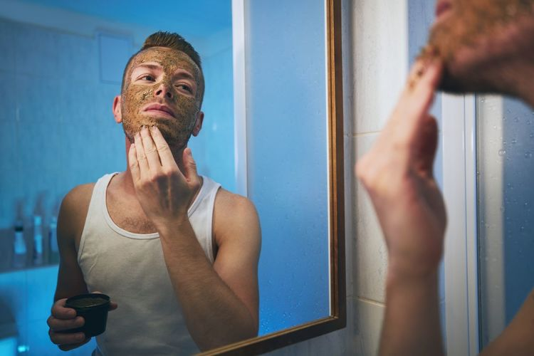 Man applying mask on face while looking in mirror at home