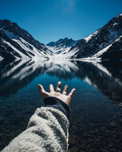 Cropped hand gesturing towards lake and snowcapped mountain against clear sky