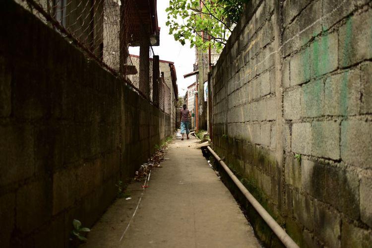 Walkway amidst buildings in city