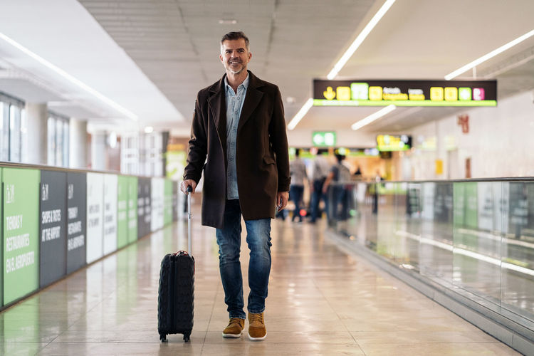 Full length portrait of young man standing at airport