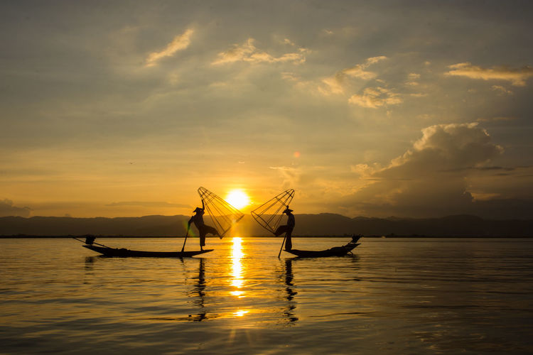 Silhouette people sailing in lake against sky during sunset
