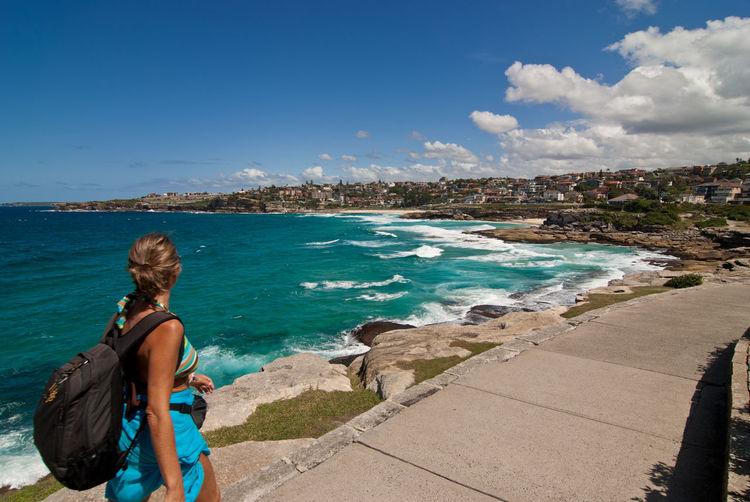 Woman walking on promenade by sea against sky