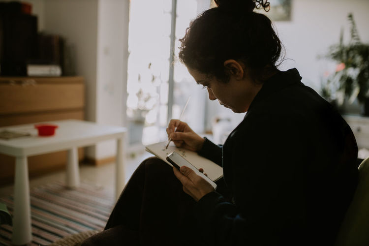Side view of woman using mobile phone and sketching at home