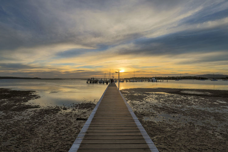 Timber jetty leading to sun setting over ocean at low tide Water Sky Cloud - Sky Sunset Scenics - Nature Pier Beauty In Nature Sea Nature Direction Tranquility Tranquil Scene The Way Forward No People Reflection Idyllic Jetty Wood - Material Outdoors Australia Australian Landscape Nature Sun Sunrise Rising Setting Evening Morning Dawn Dusk Day Outdoor