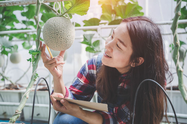 Portrait of woman holding plant
