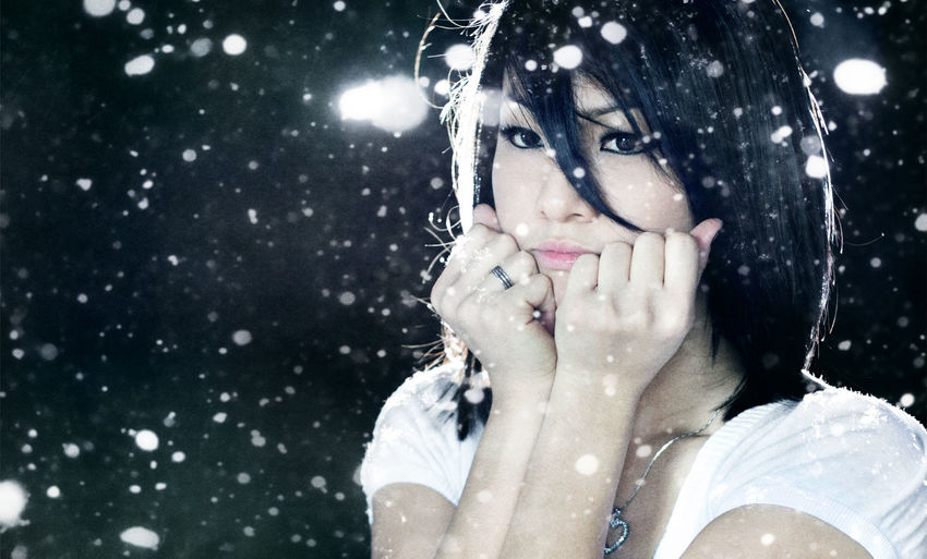Close-Up Portrait Of Young Woman Sitting Outdoors At Night During Snowfall