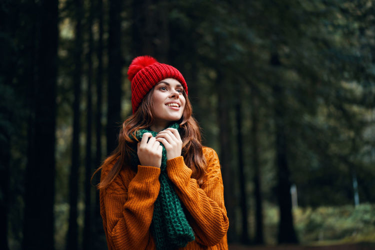 Young woman wearing hat standing in forest during winter
