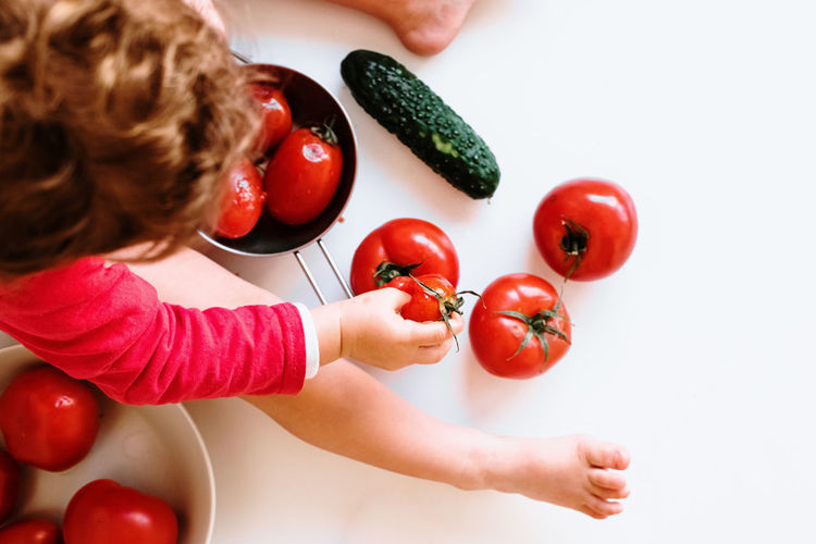 High angle view of baby with crushed tomatoes on table