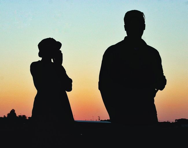 Silhouette man and woman standing against sky during sunset