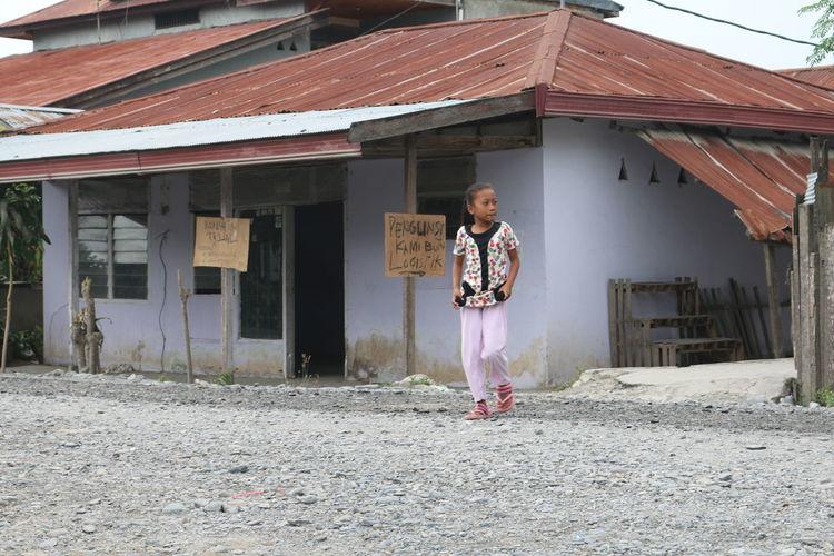 Girl walking against house in town