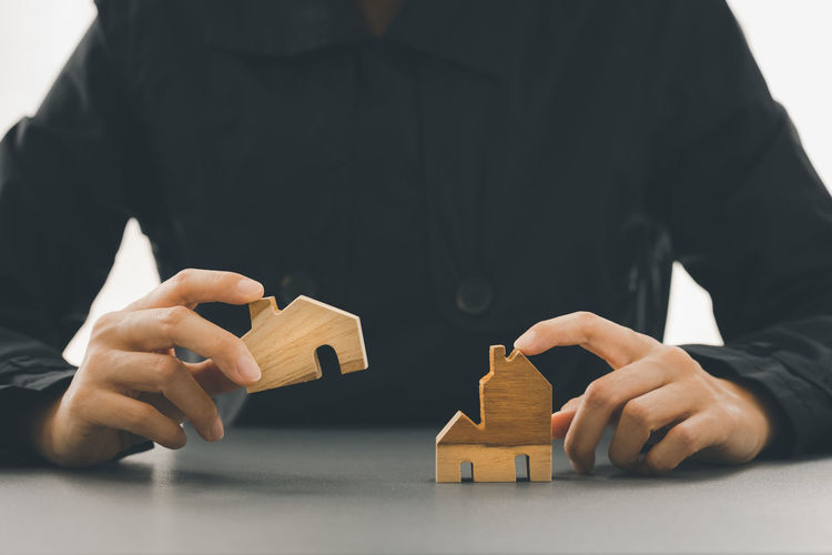Close-up of hand holding toy against house
