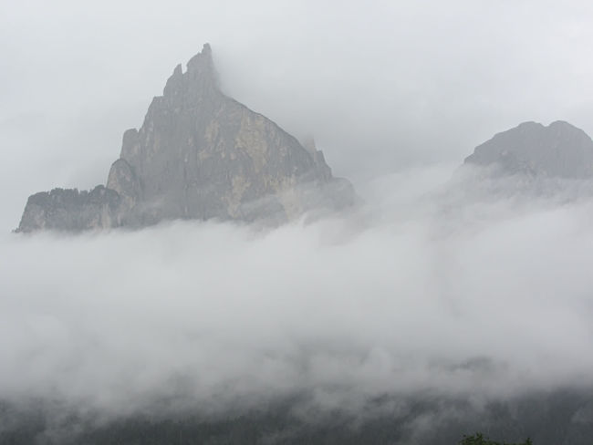 Panoramic view of the Dolomites shrouded by clouds near Castelrotto, South Tyrol - Italy Castelrotto Cliff Clouds Dolomites Fog Italy Kastelruth Landscape Majestic Mist Mountain Mountain Massif Mountain Peak Mountain Range Mountain View Pinnacle Ridge Rock Scenics Shrouded Sky Steep Storm Cloud Tyrol View