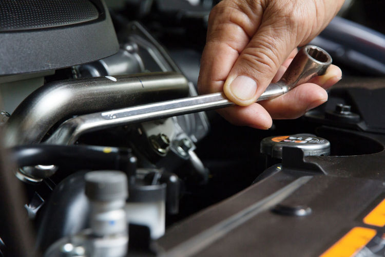 Cropped Hand Of Mechanic Repairing Car Engine With Wrench