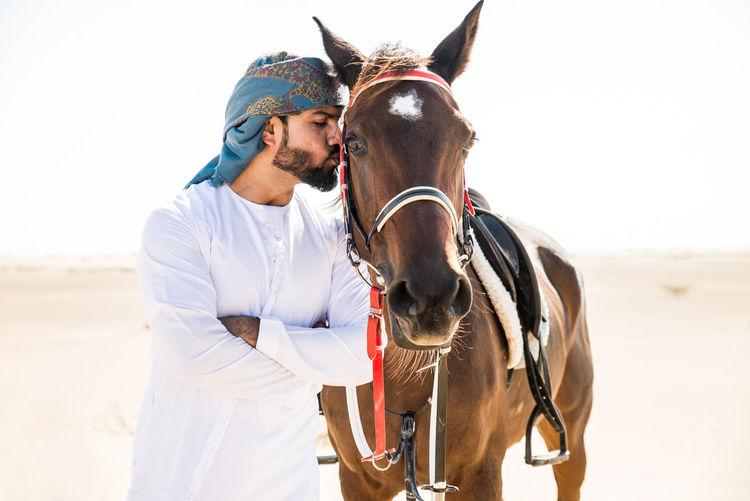 Man kissing horse in desert against sky