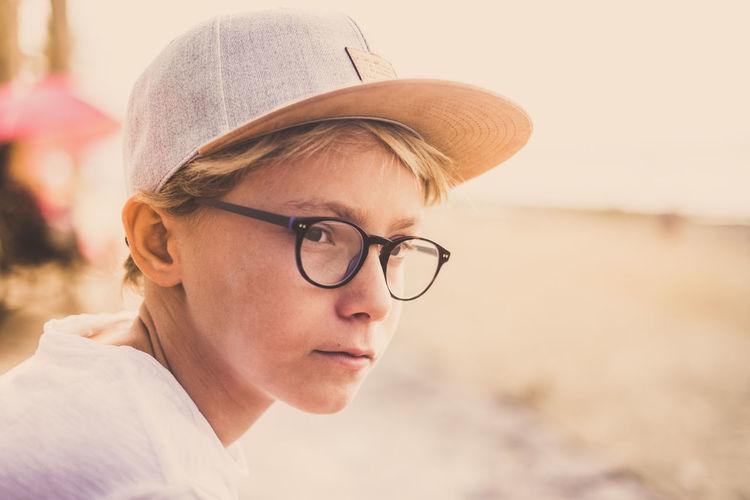 Close-up of boy wearing cap looking away