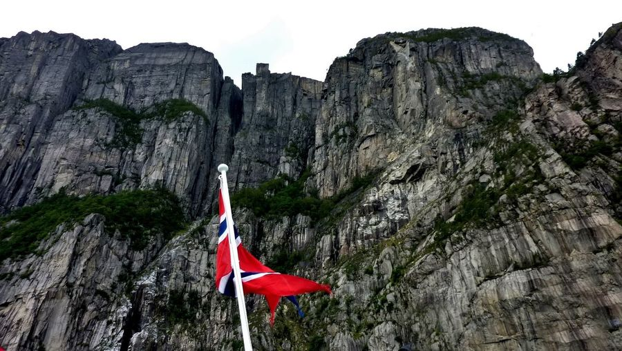 Low angle view of norwegian flags on boat against mountain of fjord with sky
