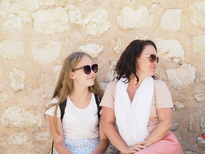 Mother and daughter wearing sunglasses while sitting against wall
