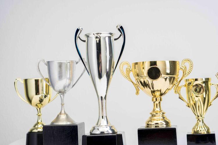 Variety of Trophy Cup on white background AWARD Trophy Studio Shot Still Life Indoors  Success Winning No People White Background Achievement Metal Gold Colored Close-up Competition Shiny Side By Side Table Silver Colored Copy Space Collection