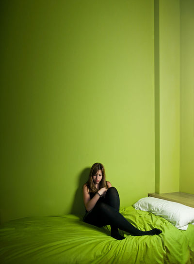 Portrait of young woman sitting on bed against wall