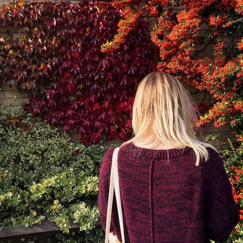 Rear View Of Woman Standing By Plants At Park