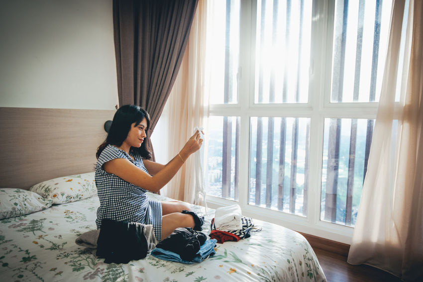 One Person Curtain Window Real People Lifestyles Full Length Sitting Indoors  Bed Furniture Home Interior Casual Clothing Leisure Activity Young Adult Day Young Women Women Side View Hairstyle