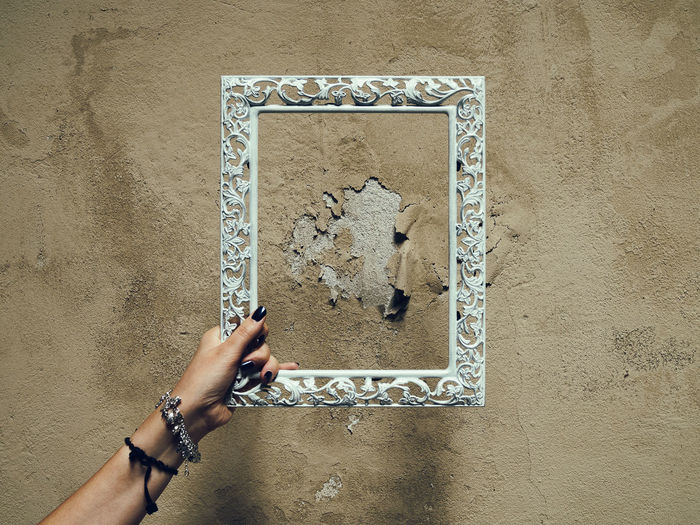 Close-Up Of Hand Holding Ornate Frame Against Weathered Wall