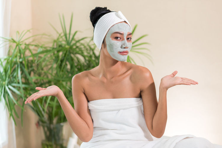Portrait of young woman with facial mask gesturing in spa