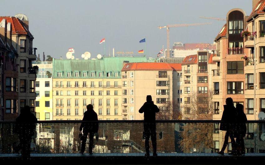 Silhouette people standing on sidewalk against city