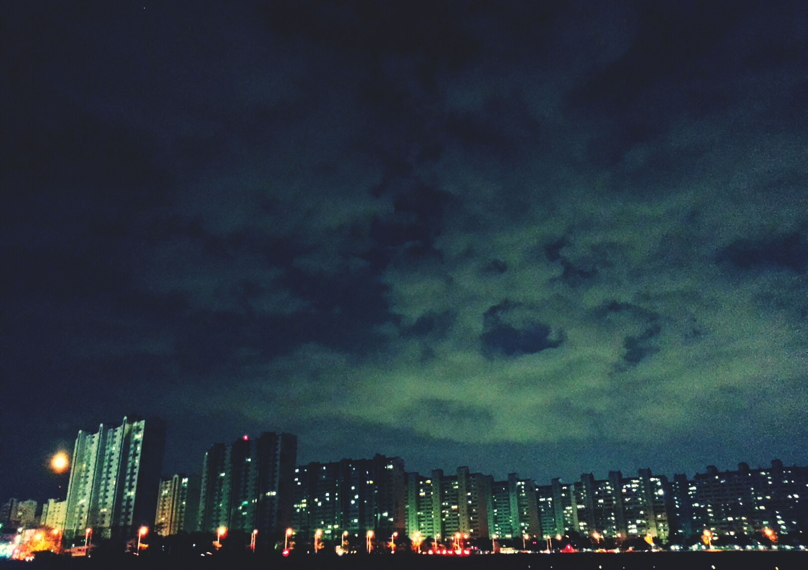illuminated, night, cityscape, city, building exterior, architecture, built structure, sky, skyscraper, crowded, urban skyline, cloud - sky, city life, residential district, modern, residential building, lightning, storm cloud, weather, outdoors