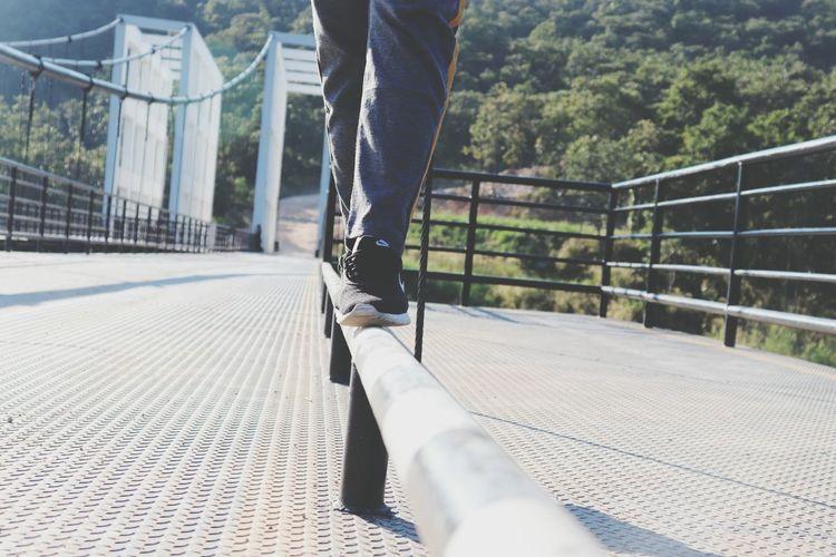 Low section of man walking on footbridge