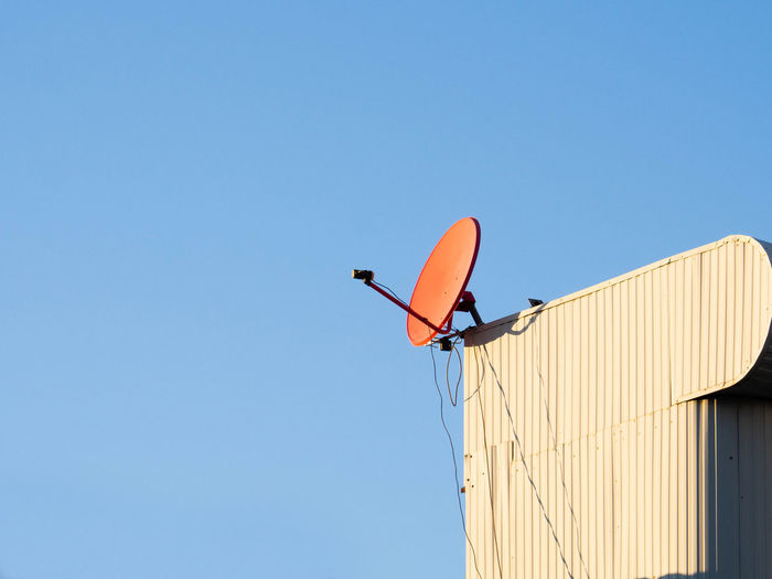 Red satellite dish hangking on roof top of building