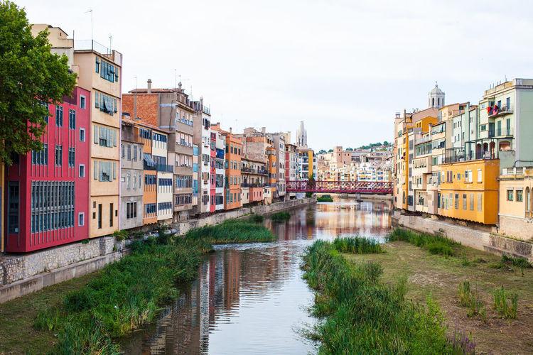 Canal amidst houses against sky