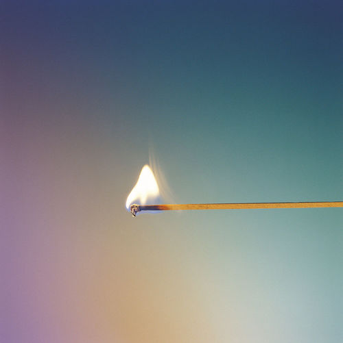 Close-up of burning matchstick against blue background