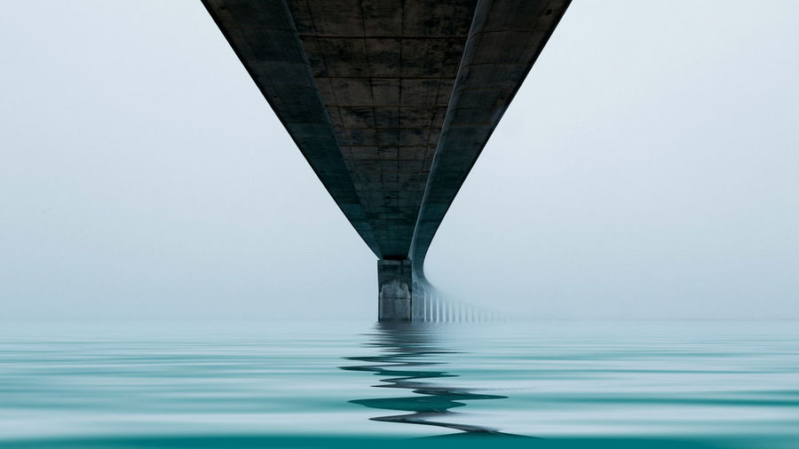Low Angle View Of Bridge Over Sea Against Clear Sky
