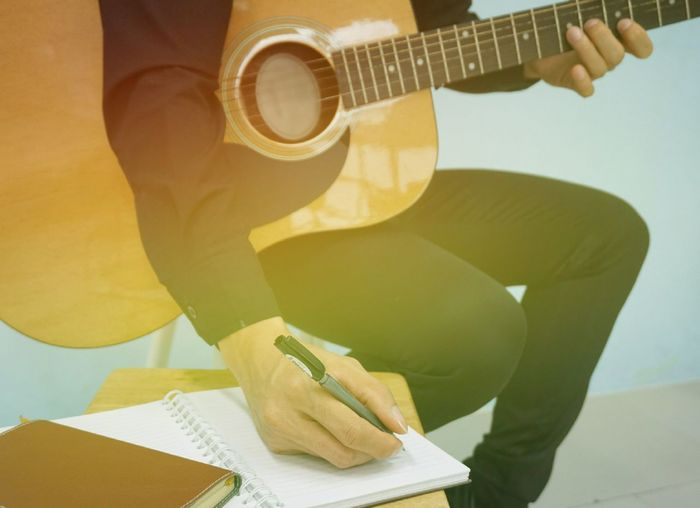 Midsection Of Man Writing In Book While Playing Guitar On Seat
