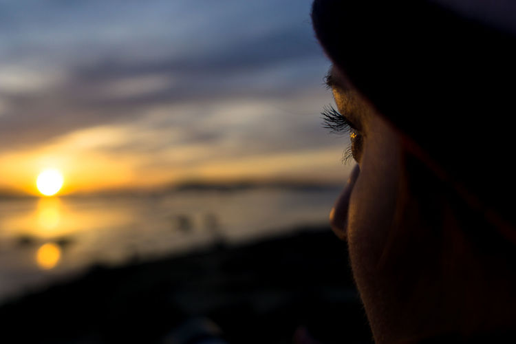Portrait of woman looking at sea during sunset
