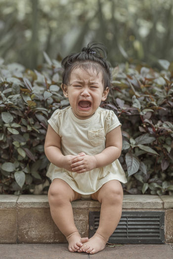 Cute baby girl crying while sitting against plants