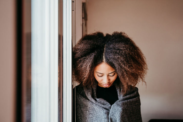 Woman with afro hair looking down by window