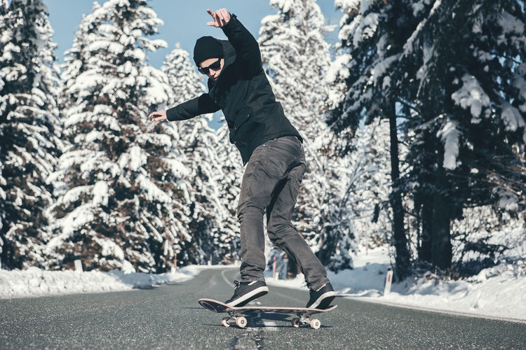 Man skateboarding in road during winter