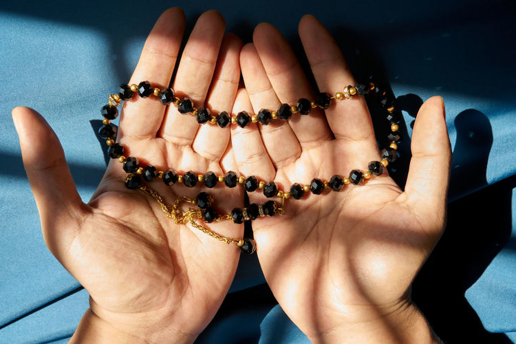 Midsection of muslim man holding rosary