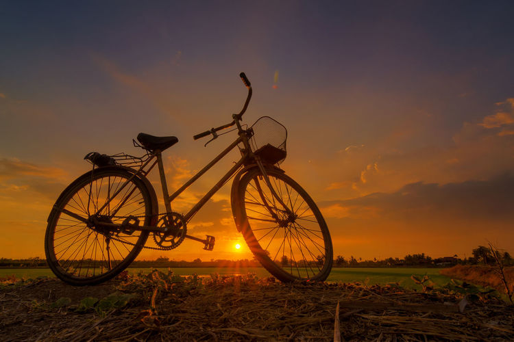 Low angle view of cycle on land against sky during sunset