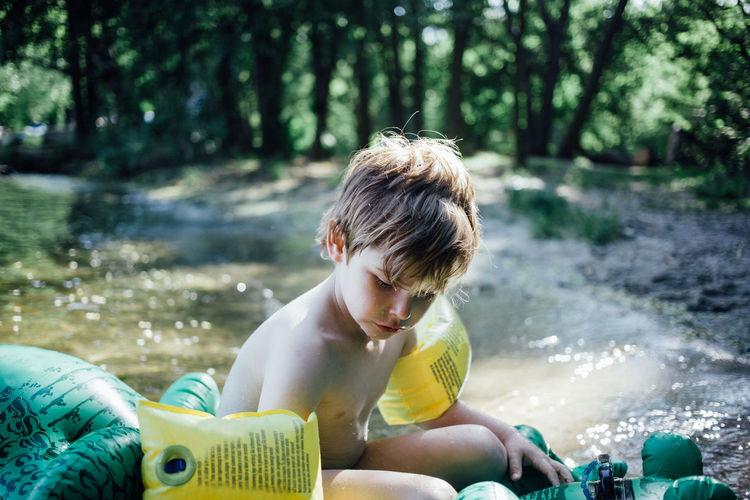 Shirtless boy wearing water wings on pool raft at lakeshore