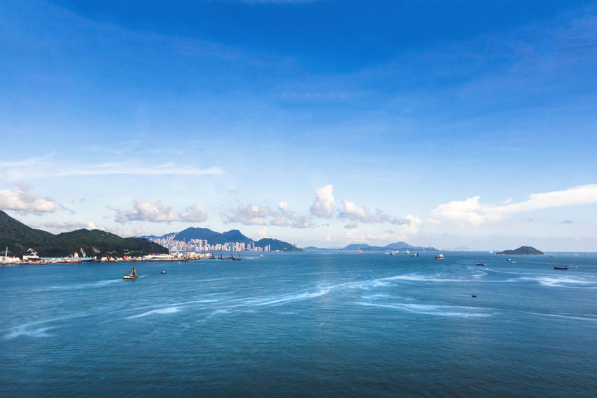 Beautiful seascape and modern building with hill at Hong Kong. Sky Water Scenics - Nature Sea Cloud - Sky Beauty In Nature Blue Mountain Tranquil Scene Tranquility Waterfront Nature No People Idyllic Transportation Non-urban Scene Day Travel Outdoors View Into Land Landscape City Boat Ship Cargo
