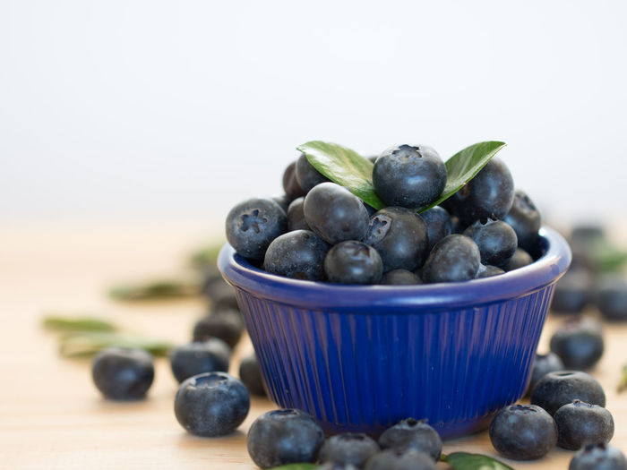 Close up fresh blueberries antioxidant organic in a blue bowl on wooden table. Agriculture; Antioxidant; Berry; Bilberry; Blue; Blueberry; Bowl; Closeup; Colour; Crop; Delicious; Dessert; Eating; Food; Fresh; Freshness; Fruit; Fruits; Green; Group; Health; Healthy; Huckleberry; Leaf; Lifestyle; Nature; Nutrition; Organic; Ripe; Supe Black Olive Blueberry Bowl Close-up Day Focus On Foreground Food Food And Drink Freshness Fruit Healthy Eating Indoors  Large Group Of Objects No People