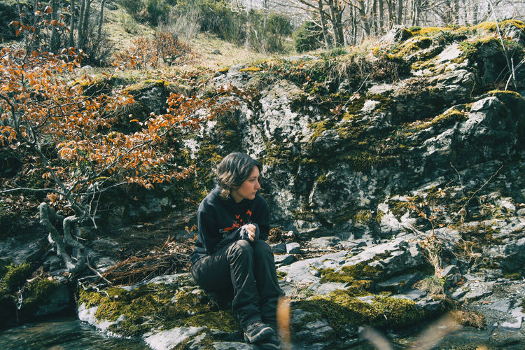 Portrait of a young girl sitting on a mossy rock next to a river in nature