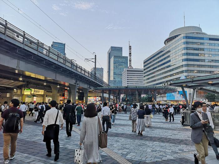 People walking on modern buildings in city against sky