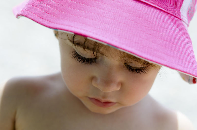 Close-up potrait of adorable little girl outdoors wearing sun hat. Child Childhood One Person Headshot Innocence Close-up Portrait Shirtless Real People Cute Pink Color Front View Boys Focus On Foreground Lifestyles Looking Looking Down Human Face