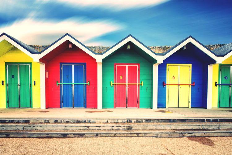 Multi colored houses on beach against sky