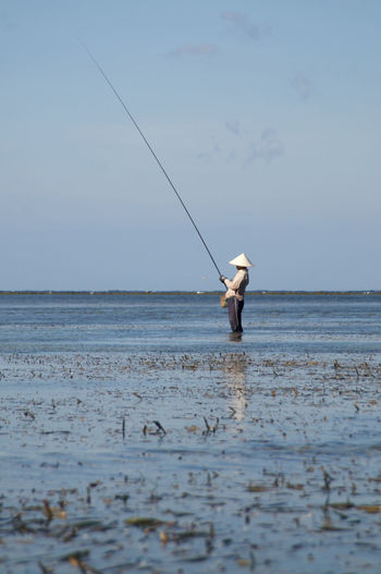 A fisherman is checking his bait Sea Water Fishing Nature Men Sky Day Standing Outdoors Low Tide Horizon Traditional Waterfront Water Reflections ASIA Asian  Balinese Fishing Rod Rod Bait Chinese Hat One Person EyeEmNewHere Bali Sanur