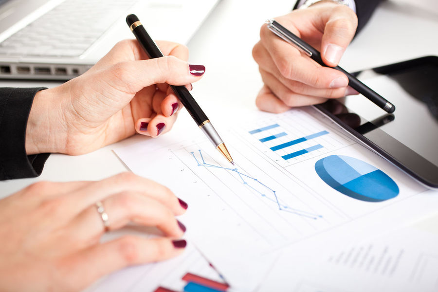 Business partners analyzing documents in their office Working Analyzing Business Finance And Industry Businessman Businesswoman Charts Colleagues Design Documents Female Finance Financial Graphs Hand Male Management Office Building Partners Pen